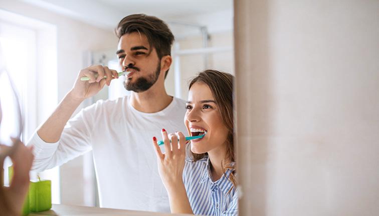 Junges Paar putzt Zähne