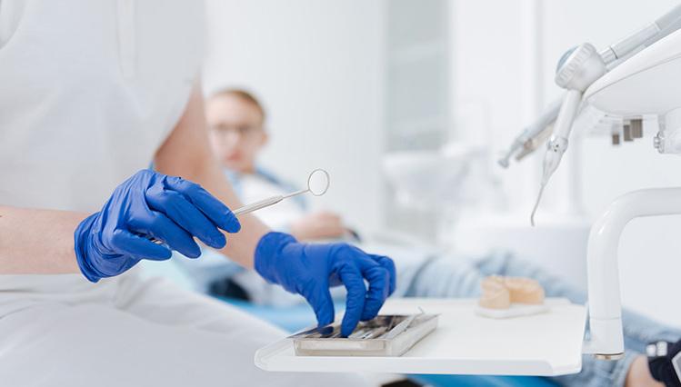 Dentalspiegel und Hände in Handschuhen