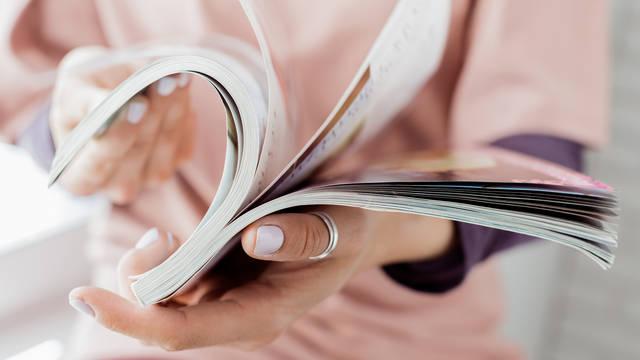 Hände blättern in einer Broschüre